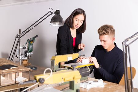 Young female architect helping male colleague making elements on scroll saw for architectural model in design bureau