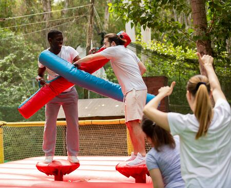 Fun wrestling with inflatable logs in an amusement park on a summer sunny day Imagens