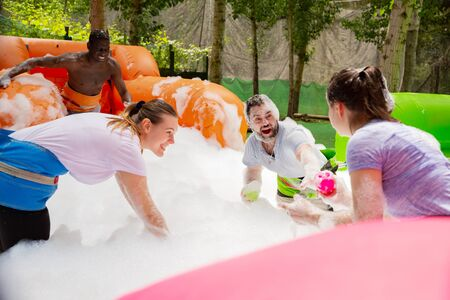 Happy friends are playing a game - who will find balls in soap suds faster