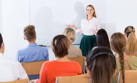 Amable joven profesora dando una conferencia a los estudiantes adultos atentos en el auditorio