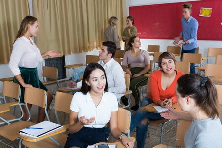 Friendly student group talking in classroom having break between lessons