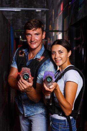 positive young couple holding colored laser guns during laser tag game in labyrinth 写真素材