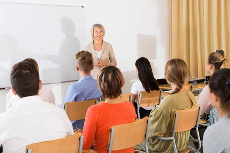 Dojrzała mówczyni prezentująca prezentację dla studentów w sali wykładowej Zdjęcie Seryjne