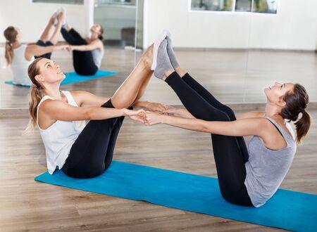 Gruppe sportlicher Menschen, die vor dem Tanztraining in einem modernen Studio zu zweit Dehnübungen machen Standard-Bild