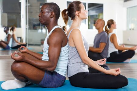 Groep volwassen mensen die rug aan rug zitten in lotusposities in moderne yogastudio Stockfoto