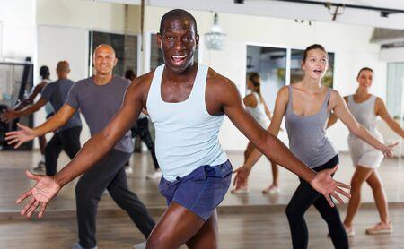 Sonriente gente joven bailando practicando swing vigoroso en dance studio