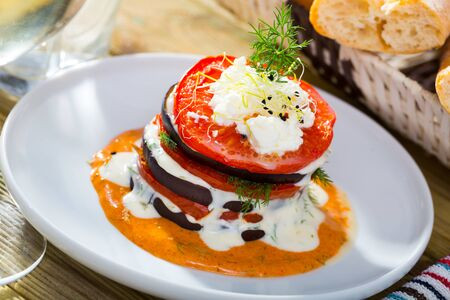 Healthy eating. Stack of fried eggplant with tomatoes, soft cheese and piquant sauce