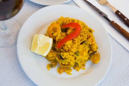 Paella with shrimp, pepper, vegetables and lemon on platter 版權商用圖片