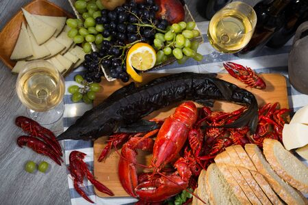 Whole smoked sturgeon fish with seafoods and white wine on wooden tabletop, top view