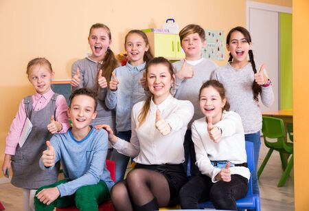 Cheerful group of pupils with female teacher posing together in schoolroom, giving thumbs up