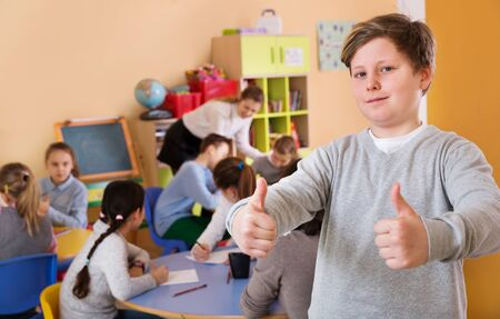 Portrait of happy schoolboy standing foreground at a classroom with studying schoolmates