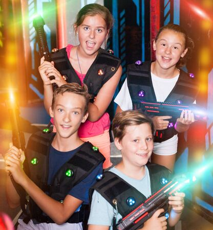 Portrait of excited teen kids with laser guns during lasertag game in dark room