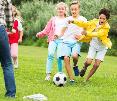 Vrolijke gelukkige kinderen joggen en voetballen in het park.