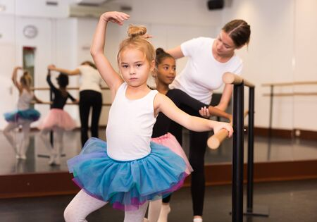 Young female classical dance teacher helping her little students near ballet barre in dancing hall