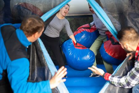 Cheerful women in big boxing gloves boxing on inflatable ring in outdoor amusement park