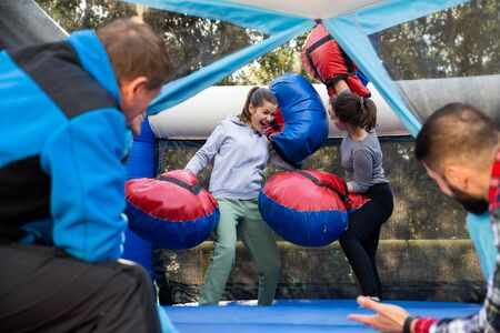 Happy female friends fighting by big stuffed boxing gloves at outdoor amusement playground