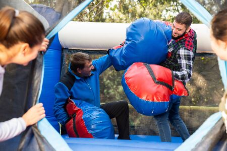 Happy male friends fighting by big stuffed boxing gloves at outdoor amusement playground Stok Fotoğraf