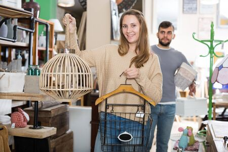 Attractive young female satisfied with purchases in furnishings store