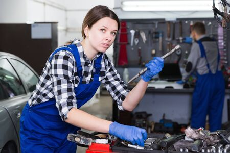 Young woman worker with instruments for repair car in workshop