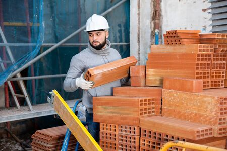 Young bearded bricklayer taking red bricks from stack in building under construction