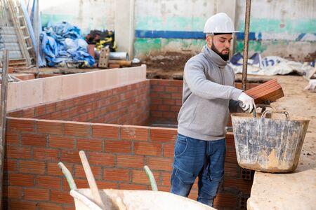 Joven concentrado trabajando en las renovaciones de su casa, instalando una pared de ladrillo en el interior