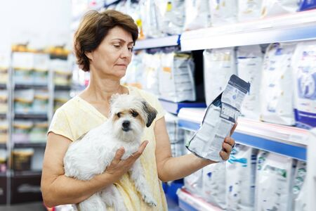 Glad woman choosing dog food for her puppy in pet supplies store
