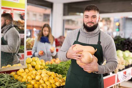 Portrait of positive man in apron selling small decorative pumpkins