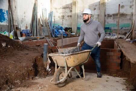 Young bearded man working at building site, carrying navvy wheelbarrow with bucket of construction mortar