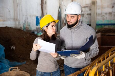 Two confident engineers discussing blueprint while standing at construction site