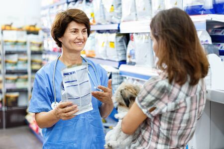 Elderly glad cheerful positive  female veterinarian recommending pet food to young woman visiting pet store with her puppy Stok Fotoğraf