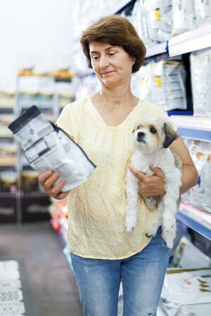 Mature woman choosing dog food for her puppy in pet supplies store Stok Fotoğraf