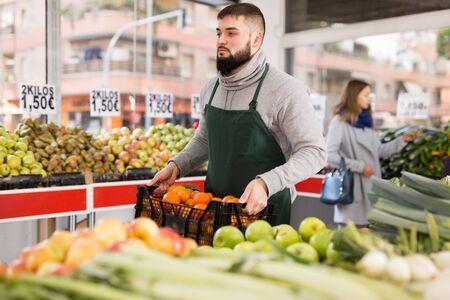 Supermarket employee carries a box of oranges Zdjęcie Seryjne