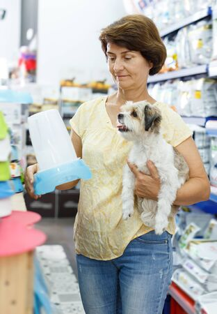 Adult woman visiting pet shop in search of dog bowl for feeding her cute havanese Stok Fotoğraf
