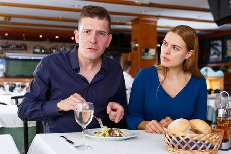 Upset couple demonstrating dissatisfaction with quality of food in restaurant Foto de archivo