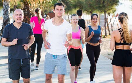 Sporty women and men running along embankment in sunny morning