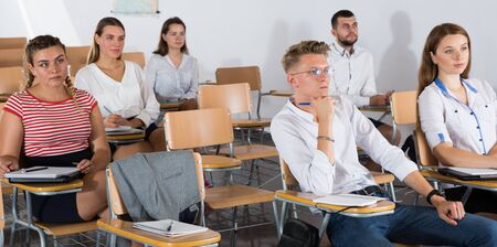 Small group of students attentively listening to lecture in classroom