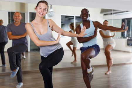 Group of happy adult people enjoying active dance movement in modern studio Stok Fotoğraf