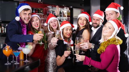 Young cheerful people with cocktails in Santa hats celebrating at nightclub