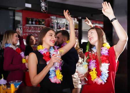 Cheerful girls dancing and toasting drinks on Hawaiian party in bar Imagens