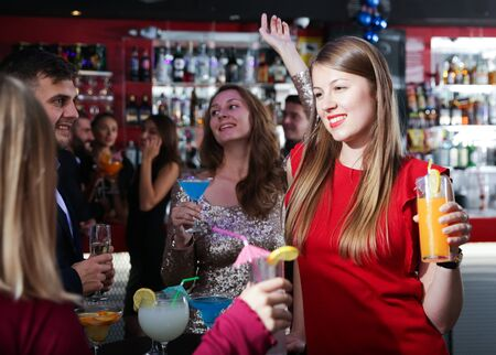 Portrait of happy young woman with colleagues enjoying corporate party in bar Imagens