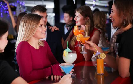 Cheerful girl with best friends partying in bar, dancing and toasting drinks Imagens