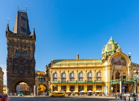 Vista del gotico medievale Torre delle Polveri (Powder Gate) collegata da un ponte ad arco aperto all'imponente Casa Municipale in Piazza della Repubblica a Praga, Repubblica Ceca