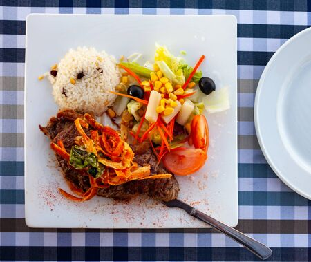 Delicious spicy veal steak with paprika and side dish of vegetable salad and white rice