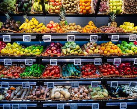 Colorful market counter with large assortment of fresh fruits and vegetables for sale
