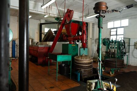 Interior of small olive oil producing factory with machine for applying olive paste on fiber mats for pressing Stock Photo