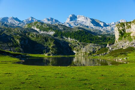 Serene landscape with one of Lakes of Covadonga and mountain range in summer day Stock Photo