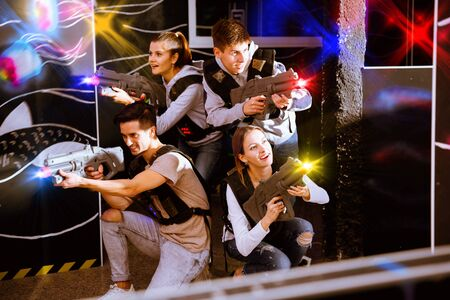 Happy glad smiling young people with laser pistols posing together on dark laser tag labyrinth