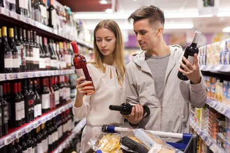 Young loving pair selecting wine for date in supermarket
