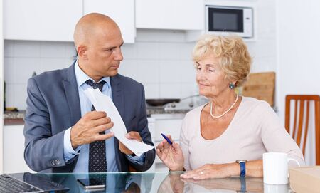 Senior woman signs document about purchase of goods in kitchen