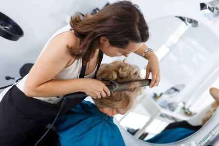 Friendly woman stylist performing hair styling with electric hair curler for senior lady in salon